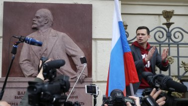 Russian opposition candidate and activist Ilya Yashin, right, speaks to a crowd next to a bas-relief of the Soviet founder Vladimir Lenin during a protest in Moscow.
