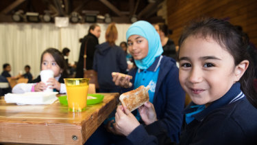 Ariana Alasi eats her toast at the free breakfast club at Campbellfield Public School.