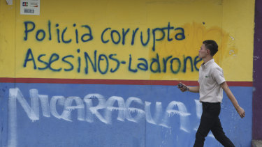 "A man walks past graffiti that reads in Spanish ""Corrupt police. Murderers-Thieves"" in Managua."
