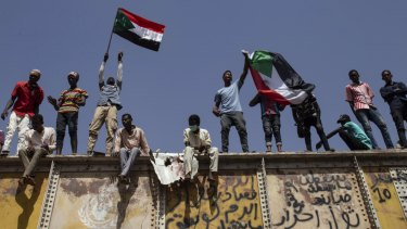 Sudanese protesters wave national flags at the sit-in outside the military headquarters in Khartoum.