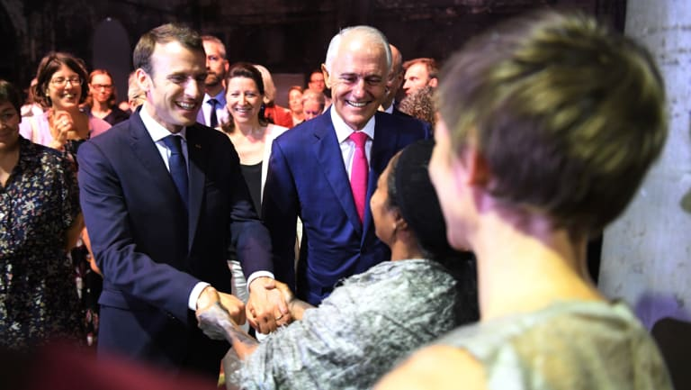 French President Emmanuel Macron, here with PM Malcolm Turnbull greeting members of Marrugeku, an indigenous Australian performance group, headed to New Caledonia on Thursday.