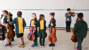 Violinist Aiko Goto, from the Australian Chamber Orchestra, with children from St Mary's North Public School.