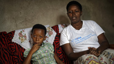 Genocide survivor Jannette Mukabyagaju, 42, recounts her experience as her daughter Natasha Umutesi, 8, listens, in their home in the reconciliation village of Mbyo.