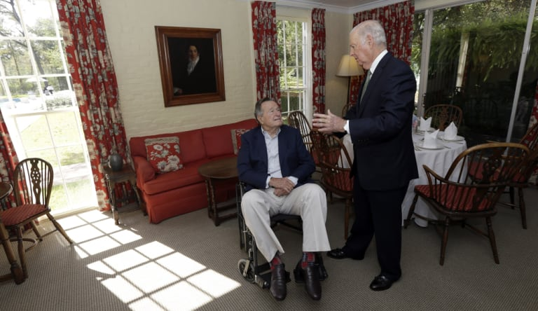 Former US president George H. W. Bush talks with his former secretary of state James Baker in 2012.