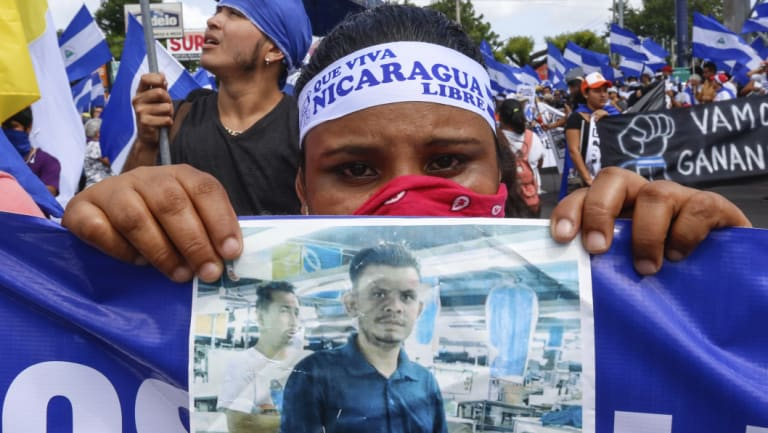 A protestor holds a photo of one of the victims of the deadly protests during an anti-government march in Managua.