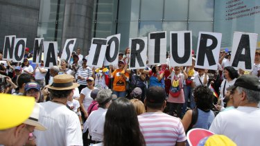 """People hold placards that spell out in Spanish: """"No more torture"""" during an opposition protest against President Nicolas Maduro in Caracas on Friday."""