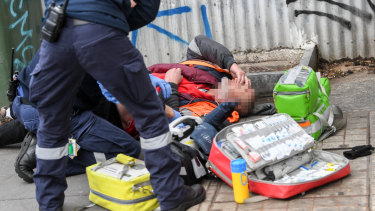 Paramedics attend to an overdose on Victoria Street last month.