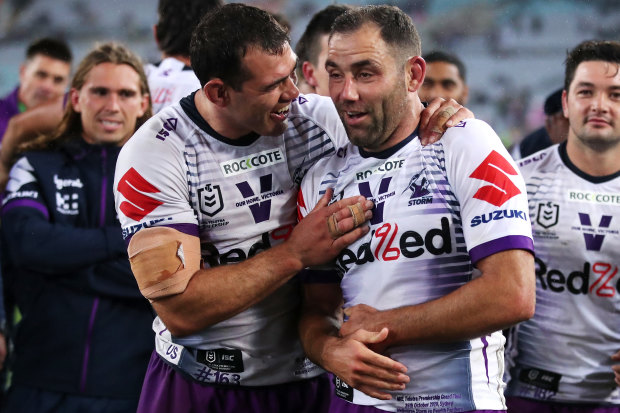 Cameron Smith appears to be holding his injured ribs during the presentation following Sunday's grand final.