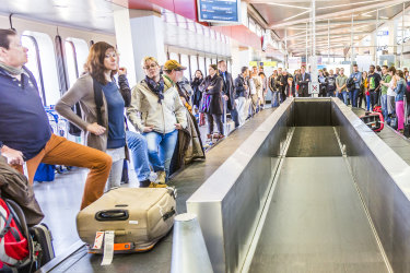 Berlin, Germany - October 27, 2014: people wait at baggage belt  in  Tegel airport, Berlin, Germany.  It is the fourth busiest airport in Germany with . over 19.59 million passengers in 2013. iStock image for Traveller. Re-use permitted. Passengers crowding around a baggage carousel at airport.
