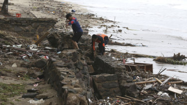 Indonesian rescuers search for the bodies of tsunami victims in Carita, Indonesia.