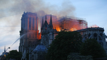 A firefighter tackles the blaze as flames and smoke rise from Notre-Dame cathedral as it burns in Paris.