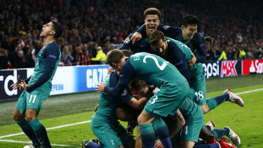 Triumphant: Tottenham players following Moura's third and decisive strike.