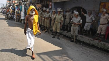 A Hindu holyman walks past Indian security men standing guard in Ayodhya, India, during clashes in 2010.