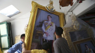 Thai workers prepare to transport a giant portrait of Thailand's King Maha Vajiralongkorn in the lead up to his coronation.