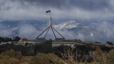 Parliament House with snow-dusted mountains surrounding the ACT after a blizzard delivered snow overnight in Canberra and parts of NSW.