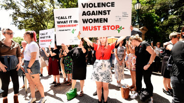 Protesters hold placards during a domestic violence protest organised by The Red Rose Foundation in Brisbane, Friday, February 21, 2020.