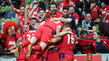 Reds ahead: Nikola Mileusnic celebrates with teammates and away fans after opening the scoring for Adelaide.