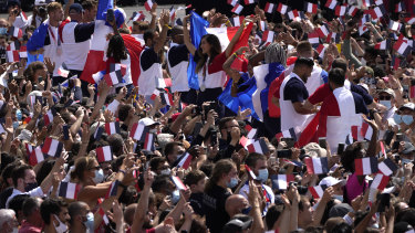 Fans wave French flags and cheer in the Olympics fan zone at Trocadero Gardens in front of the Eiffel Tower.