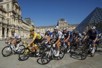 Yellow jersey Tadej Pogacar leads the peloton past the Louvre on Sunday.