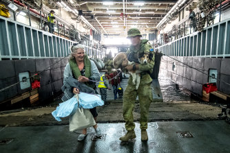 Evacuees board HMAS Choules for the trip back to Melbourne.