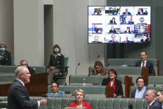 """Prime Minister Scott Morrison responds to a question as """"remote"""" MPs hover over the chamber."""