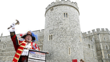 An unofficial Town Crier announces the birth of Baby Sussex outside Windsor Castle.