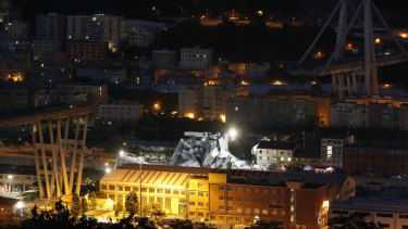 Lamps illuminate the area where rescue teams search for survivors in the rubble of the collapsed Morando highway bridge in Genoa.