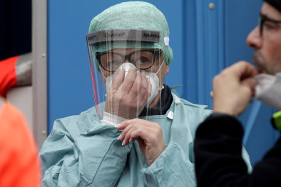 Medical staff wearing protective masks work at one of the emergency structures that were set up to ease procedures at the Brescia hospital, northern Italy.