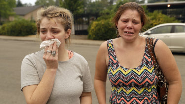 Sherry Bledsoe, left, cries next to her sister, Carla, outside the sheriff's office after hearing news that Sherry's children, James and Emily, and grandmother, Melody Bledsoe, were killed in the fire on Saturday.