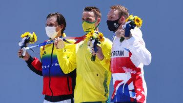 Silver medallist Daniel Dhers of Venezuela, gold medallist Logan Martin of Australia, and bronze medallist Declan Brooks of Great Britain on the podium after their men's park final of the BMX freestyle in Tokyo.