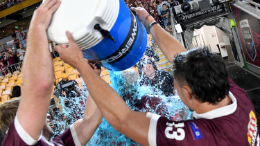 Maroons coach Wayne Bennett has an ice bucket poured on him by Tino Fa'asuamaleaui and Christian Welch.