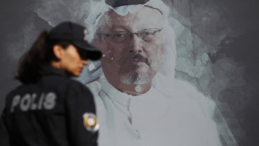 A Turkish police officer walks past a picture of slain Saudi journalist Jamal Khashoggi before a ceremony, near the Saudi Arabia consulate in Istanbul, marking the one-year anniversary of his death.