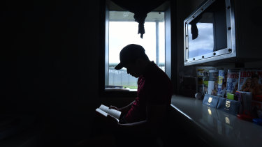 A detainee reads a book inside his room at Cobham Juvenile Justice Centre in Sydney's west.