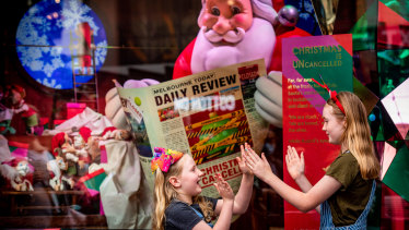 Santa catches up on the news in the Myer Christmas windows.
