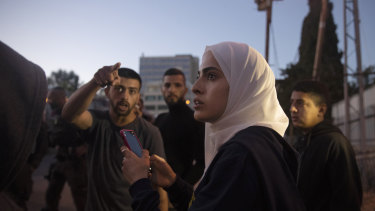 Palestinian activist Muna al-Kurd, centre, stands with other activists as Israeli police approach their friends repairing a mural that was defaced by a Jewish settler, in the Sheikh Jarrah neighborhood of east Jerusalem.