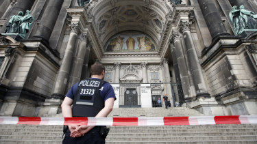 A police officer stands in front of the Berlin Cathedral in on Sunday.