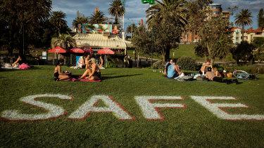 Melburnians enjoy the sun at St Kilda beach while social distancing.