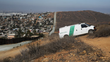 A US Border Patrol van drives up the hill on the US side to pick up migrants apprehended trying to cross from Mexico, left, illegally.