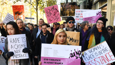 Protesters hold placards as they march through Melbourne to protest violence against women.