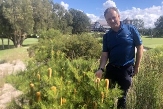Royal Sydney Golf Club landscape architect Harley Kruse next to a patch where the grass was ripped out, watering was stopped and native plants were replanted and self-seeded in the sand.