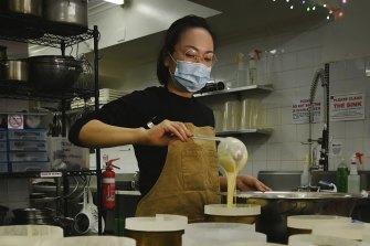 Naoka Kojo, co-creator of 15centimeters, prepares cheesecakes for baking.