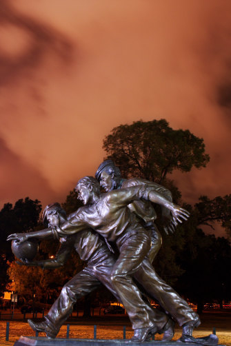 A statue depicting the first game of Australian rules football. Tom Wills is on the right in the cap.