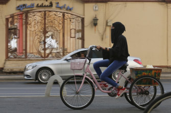 A Saudi Arabian woman rides a bicycle in Jeddah. Foreign women will be asked to dress modestly, but will not be forced to wear a niqab or abaya.