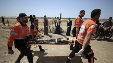 Palestinian medics evacuate a wounded man during a protest by the Israeli border with Gaza Strip on Wednesday.