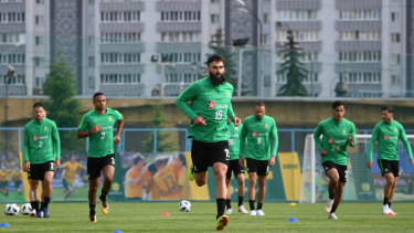 Leading the way: Mile Jedinak strides out with the Socceroos squad at their base in Kazan.