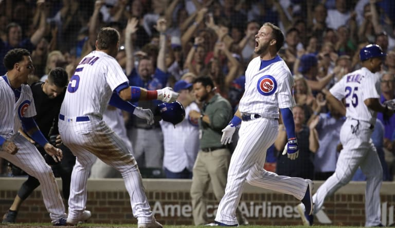Chicago Cubs' David Bote, right, reacts as he celebrates with teammates after hitting the game-winning grand slam during the ninth inning of a baseball game against the Washington Nationals.
