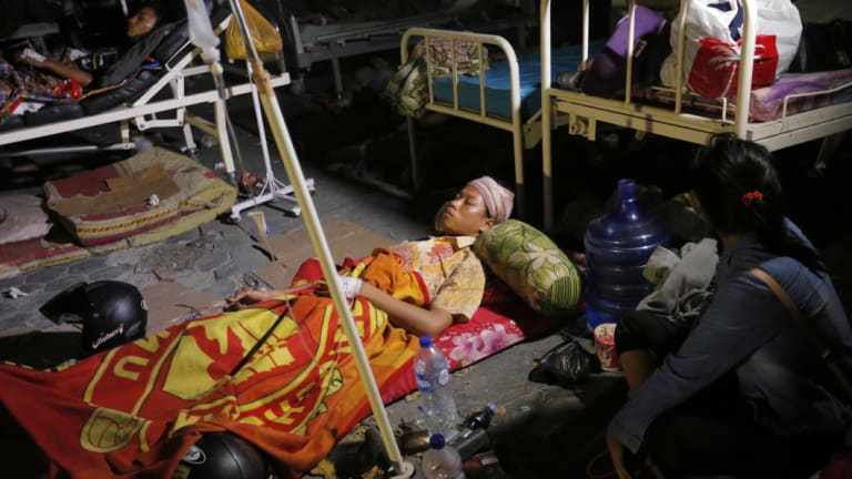 A woman lays while being treated outside at Army hospital following earthquakes and a tsunami in Palu, Central Sulawesi.