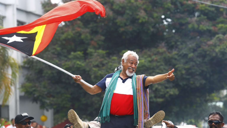 East Timorese independence hero Xanana Gusmao waves a national flag in Dili last month.