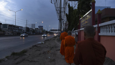 Female Theravada Buddhist monks walk the streets on their alms round - food offerings from locals that they will take back to the Songdhammakalyani Monastery to share.