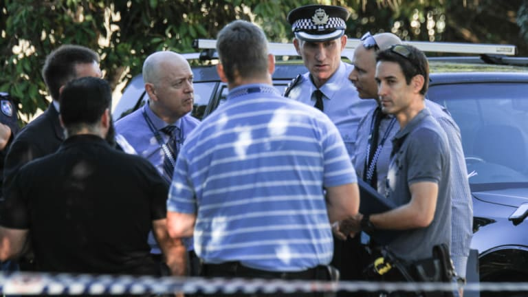 Police Inspector Daniel Bragg (second from right) speaks with fellow officers at the scene.